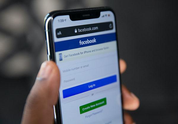 Pessoa segurando celular com tela de login do Facebook